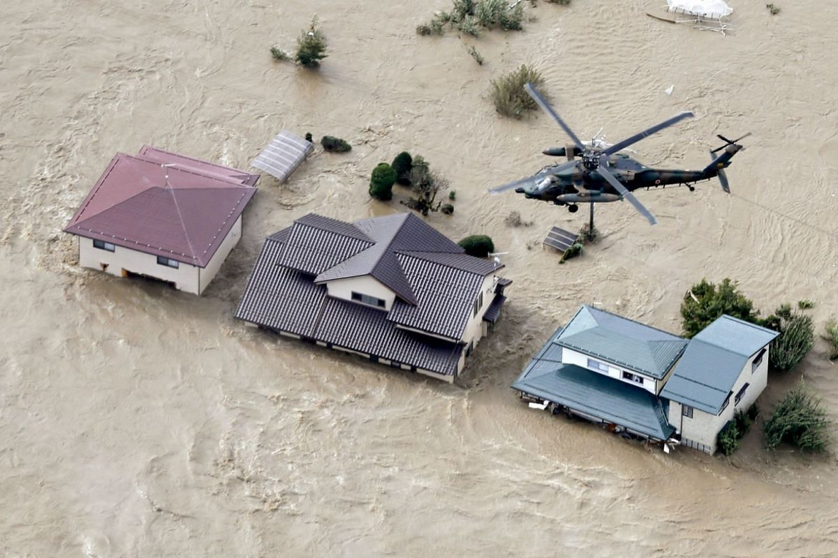 A Japan Self-Defence Force helicopter flying over residential areas flooded by the Chikuma river as Typhoon Hagibis hits Nagano, on Oct 13, 2019.