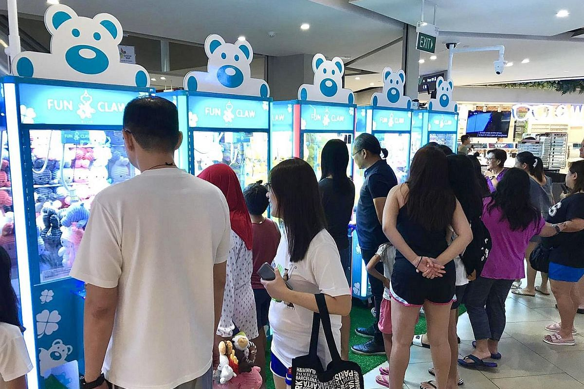 Fun Mall visitors at claw machines by Fun Claw on level one of The Seletar Mall (above).