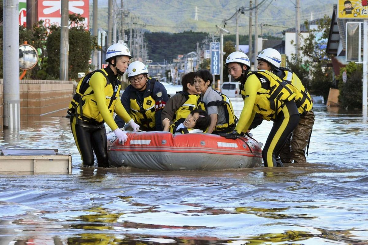Local residents sit in a boat as they are rescued from a flooded residential area in Iwaki, Fukushima prefecture on Oct 13, 2019.