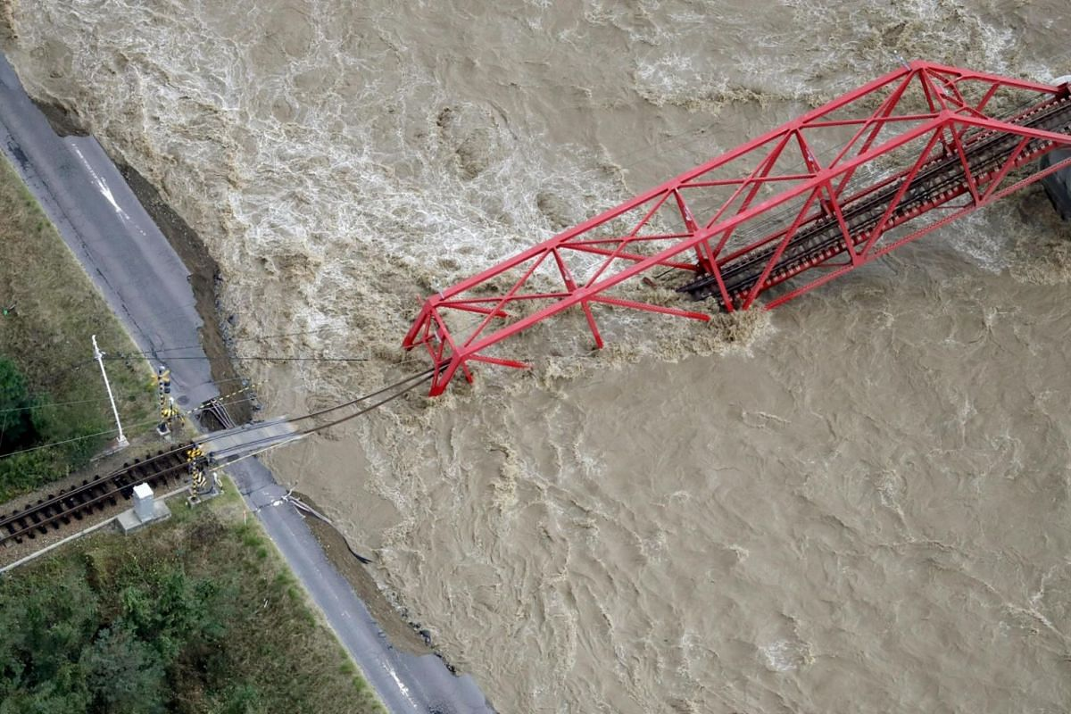 A collapsed railway bridge is seen over Chikuma river swollen by Typhoon Hagibis in Ueda on Oct 13, 2019.