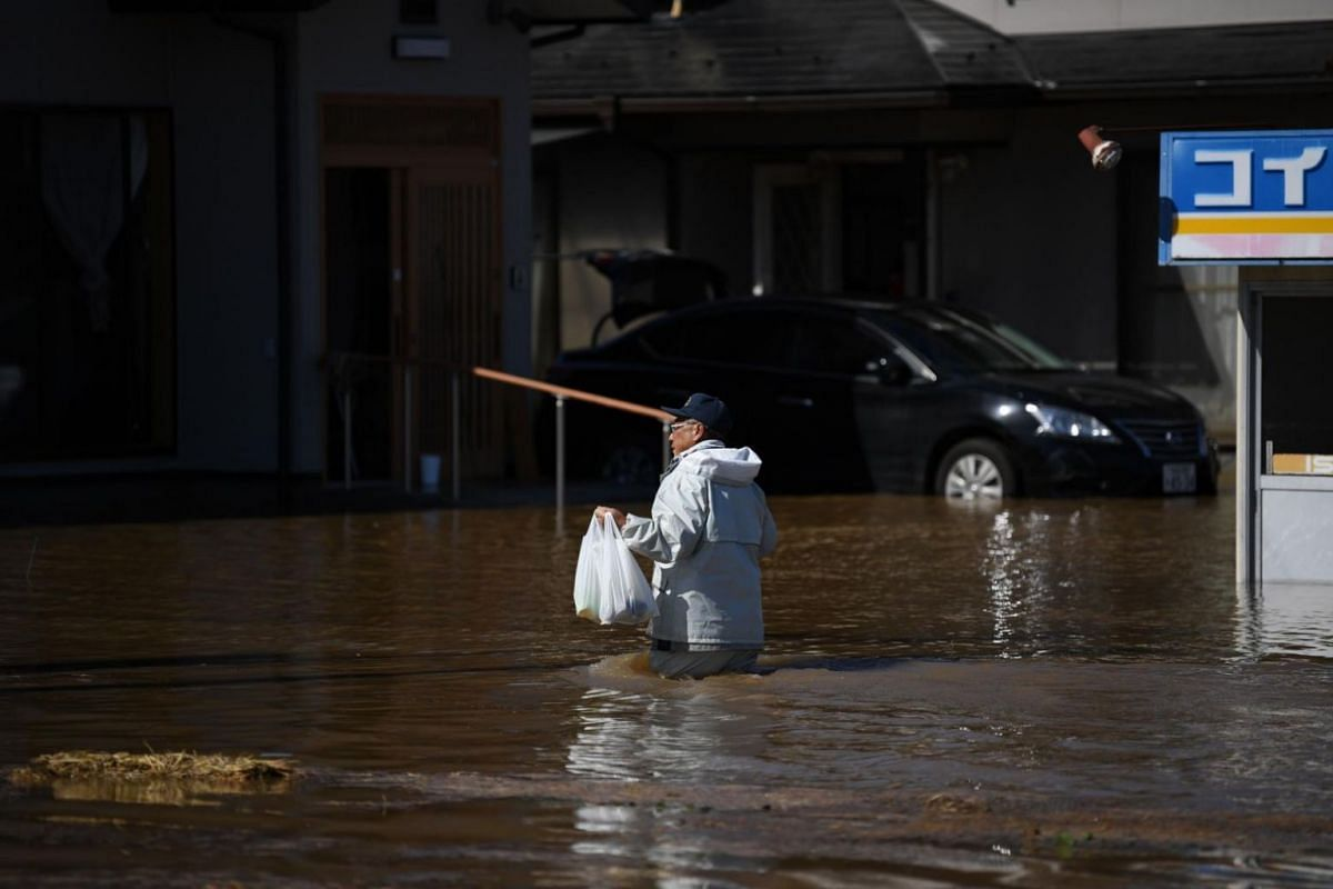 A man, carrying food to be distributed to residents trapped in their homes, wades through floodwaters in the aftermath of Typhoon Hagibis in Shibata district, Miyagi Prefecture on Oct 13, 2019.