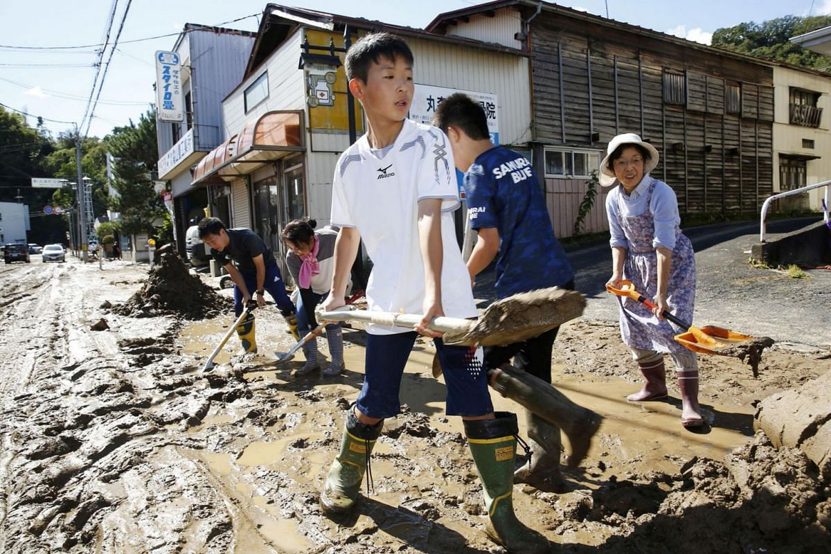 Schoolchildren and residents remove mud after flooding caused by Typhoon Hagibis in Marumori, Miyagi prefecture on Oct 13, 2019.