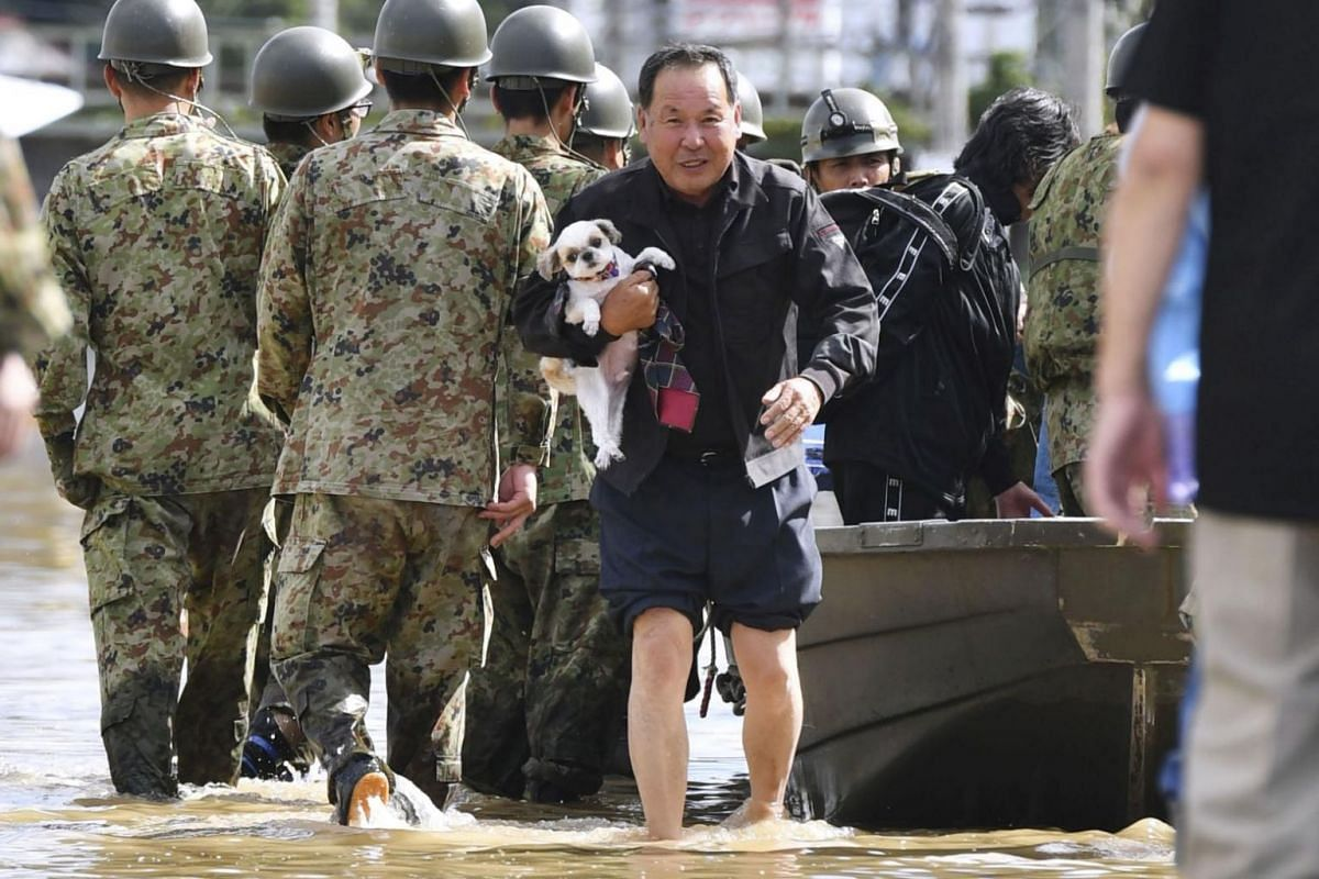 A local resident carrying his pet dog evacuates from an area flooded by the Abukuma river in Motomiya, Fukushima prefecture on Oct 13, 2019.