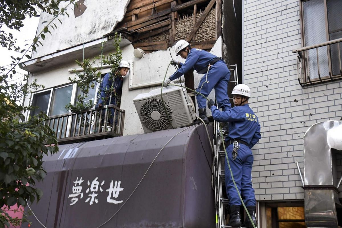 Tokyo Fire Department workers help repair damage in the aftermath of Typhoon Hagibis, in Kawasaki on Oct 13, 2019.