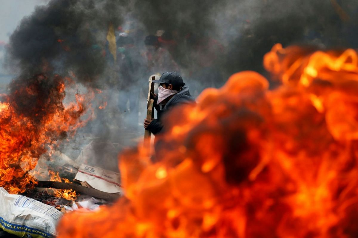 A demonstrator stands near a fire during a protest against Ecuador's President Lenin Moreno's austerity measures in Quito, Ecuador October 12, 2019. PHOTO: REUTERS