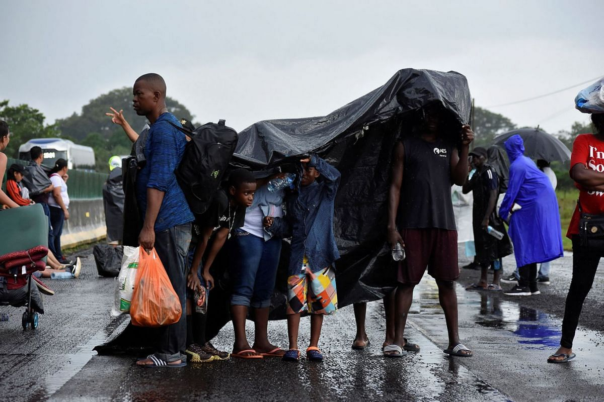 Migrants shelter from the rain as members of the National Guard (not pictured) conduct an operation to halt a caravan of migrants from Africa, the Caribbean and Central America, hours after they embarked toward the United States, in Tuzantan, in Chia