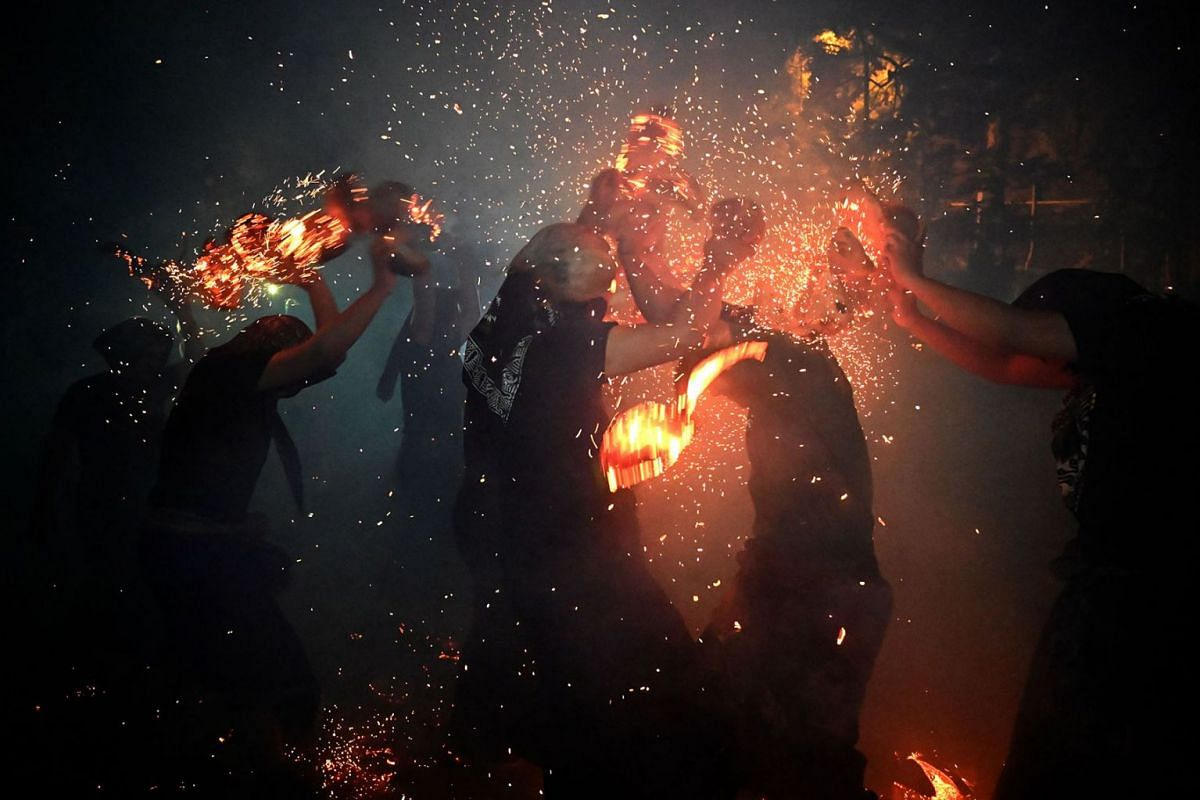 This picture taken on October 13, 2019 shows Balinese youths participating in a fire war ceremony, locally known as Siat Geni, at a temple in Tuban near Denpasar on Indonesia's resort island of Bali. PHOTO: AFP