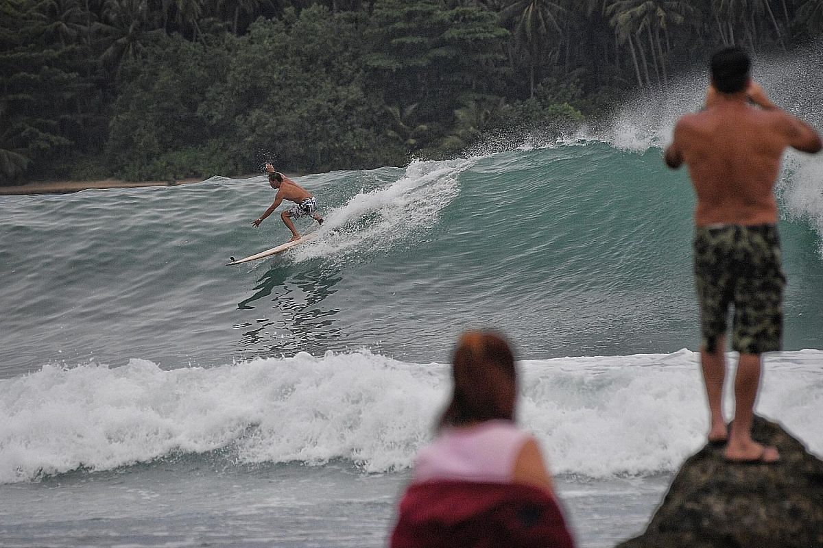 """Mr Eu catching a wave at Sorake Bay. He has been returning to the bay since his first visit nearly three decades ago. """"The waves here are first-class,"""" he says."""