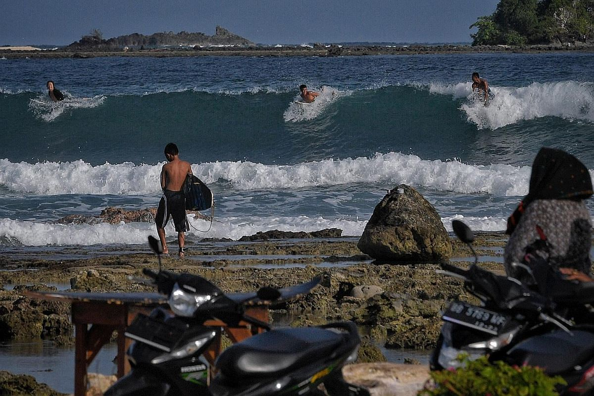 Above: Foreign and local surfers preparing to drop in on a wave at Sorake Bay. During the peak surfing season from June to October, up to 40 people at a time can be seen in the water waiting for waves. Right: A local surfer heading home at dusk. Sora