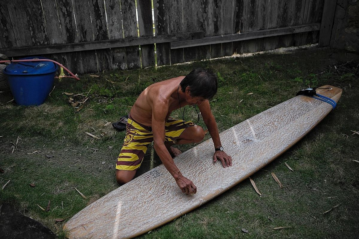 Mr Eu applying wax on his board which measures nearly 3m long. Surfers who use longboards usually surf on more mellow waves, making him a rather peculiar sight in Nias where most surfers ride shorter boards with a more aggressive style. Every morning