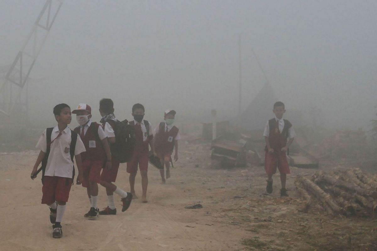 Schoolchildren make their way to school as haze from forest fires blankets Palembang, Indonesia, on October 14, 2019. PHOTO: AFP