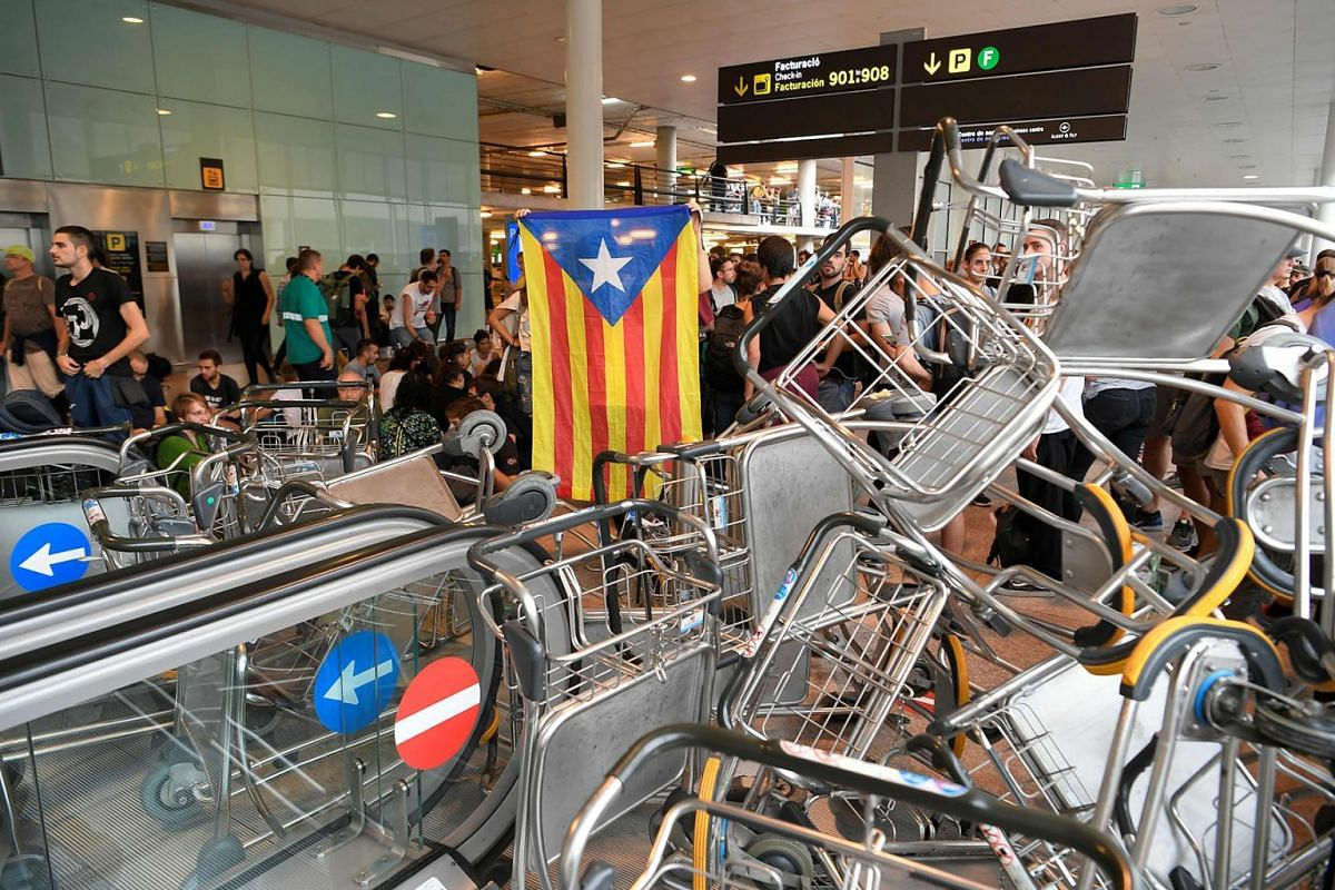 Protesters use trolleys to block escalators at El Prat airport in Barcelona on October 14, 2019 as thousands of angry protesters took to the streets after Spain's Supreme Court sentenced nine Catalan separatist leaders to between nine and 13 years in