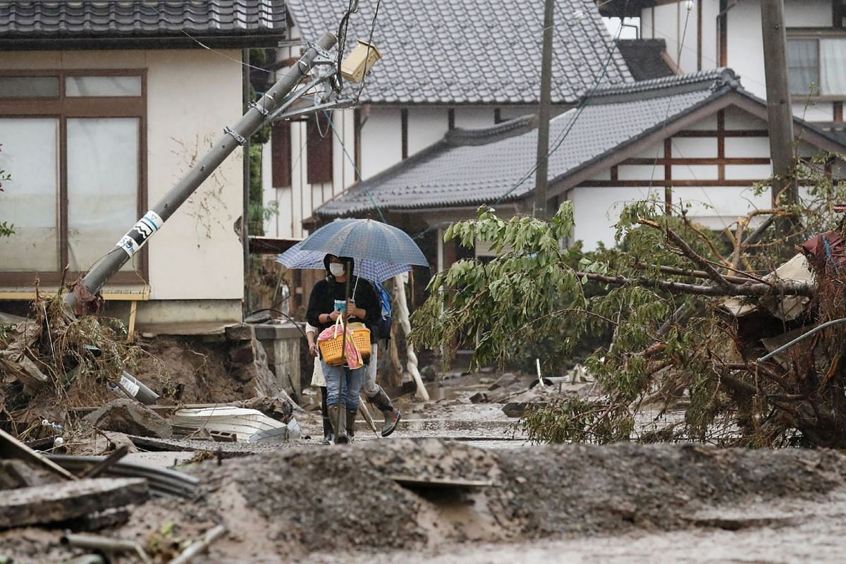In this picture taken on October 14, 2019 a resident walks through a typhoon affected area near the Chikuma river bank in Nagano after Typhoon Hagibis crashed into Japan on October 12, unleashing high winds and torrential rain across 36 of the countr