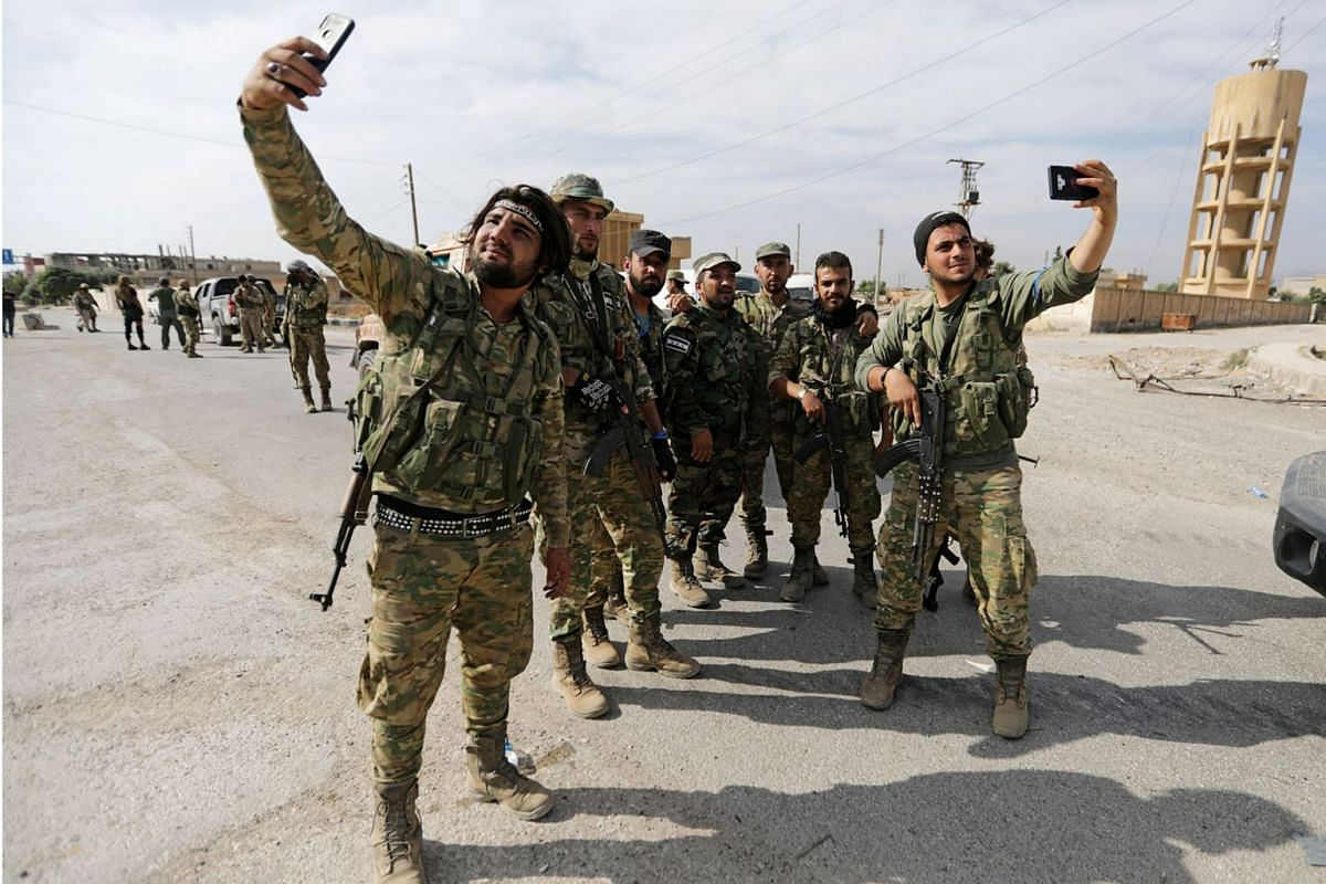 Turkey-backed Syrian rebel fighters take pictures with mobile phones at the border town of Tel Abyad, Syria, October 14, 2019. PHOTO: REUTERS