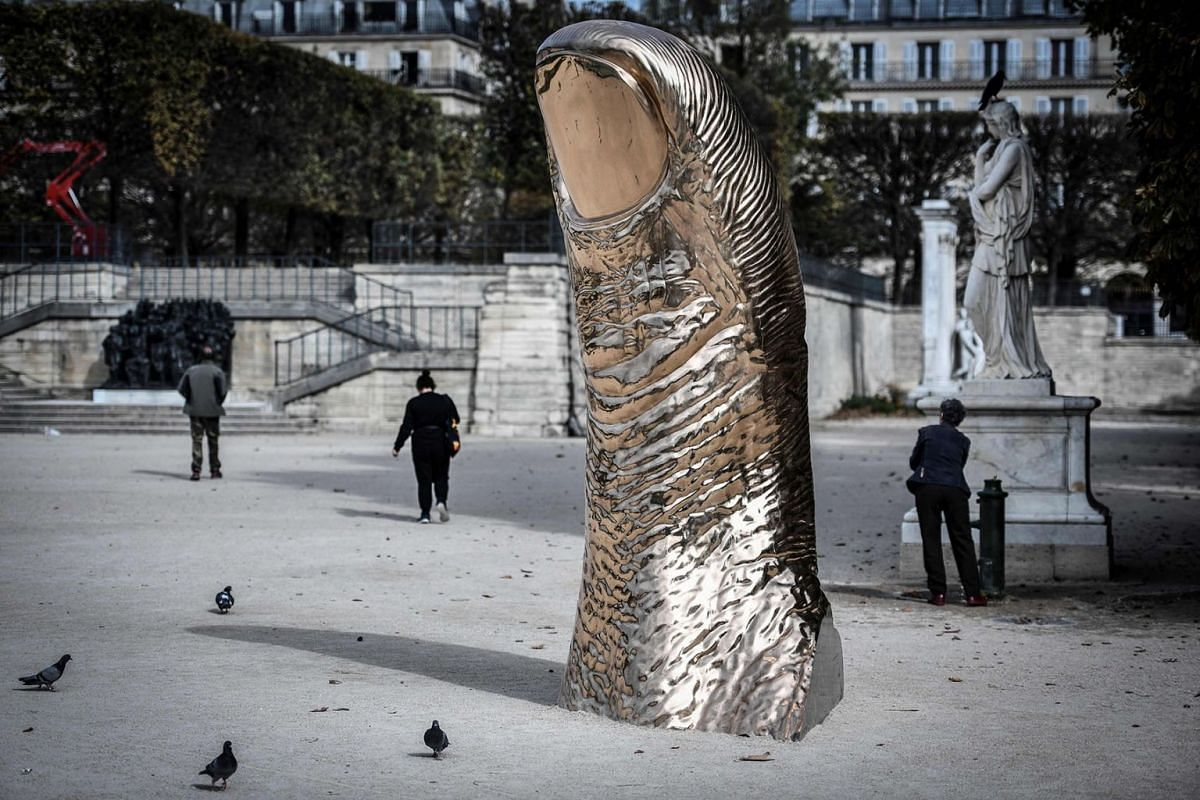 """People walk next to the artwork 'Pouce 1998-2019' by French artist Cesar at The Jardin des Tuileries in Paris, on October 14, 2019, on display as part of the """"FIAC Hors les Murs"""" event, ahead of the official opening of Europe's biggest contemporary a"""
