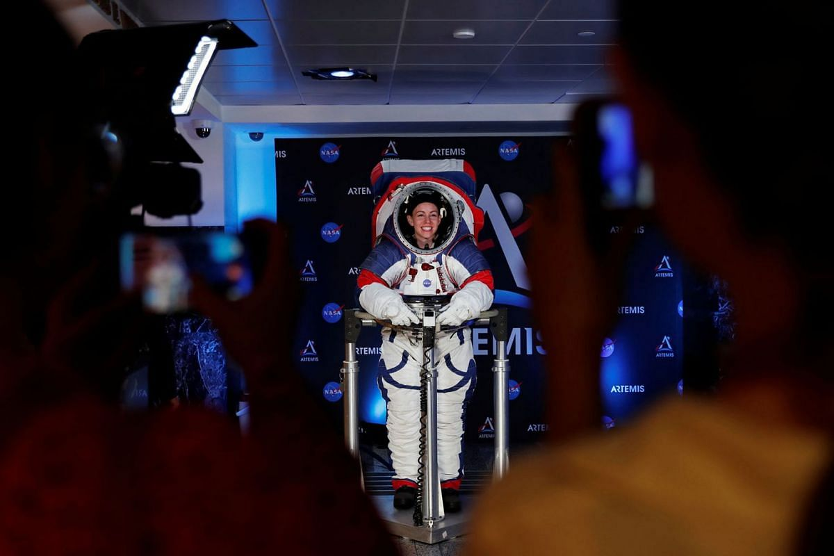 Visitors take pictures of Advanced Space Suit Engineer at NASA Kristine Davis as she wears the xEMU prototype space suit for the next astronaut to the moon by 2024, during its presentation at NASA headquarters in Washington, U.S., October 15, 2019. P