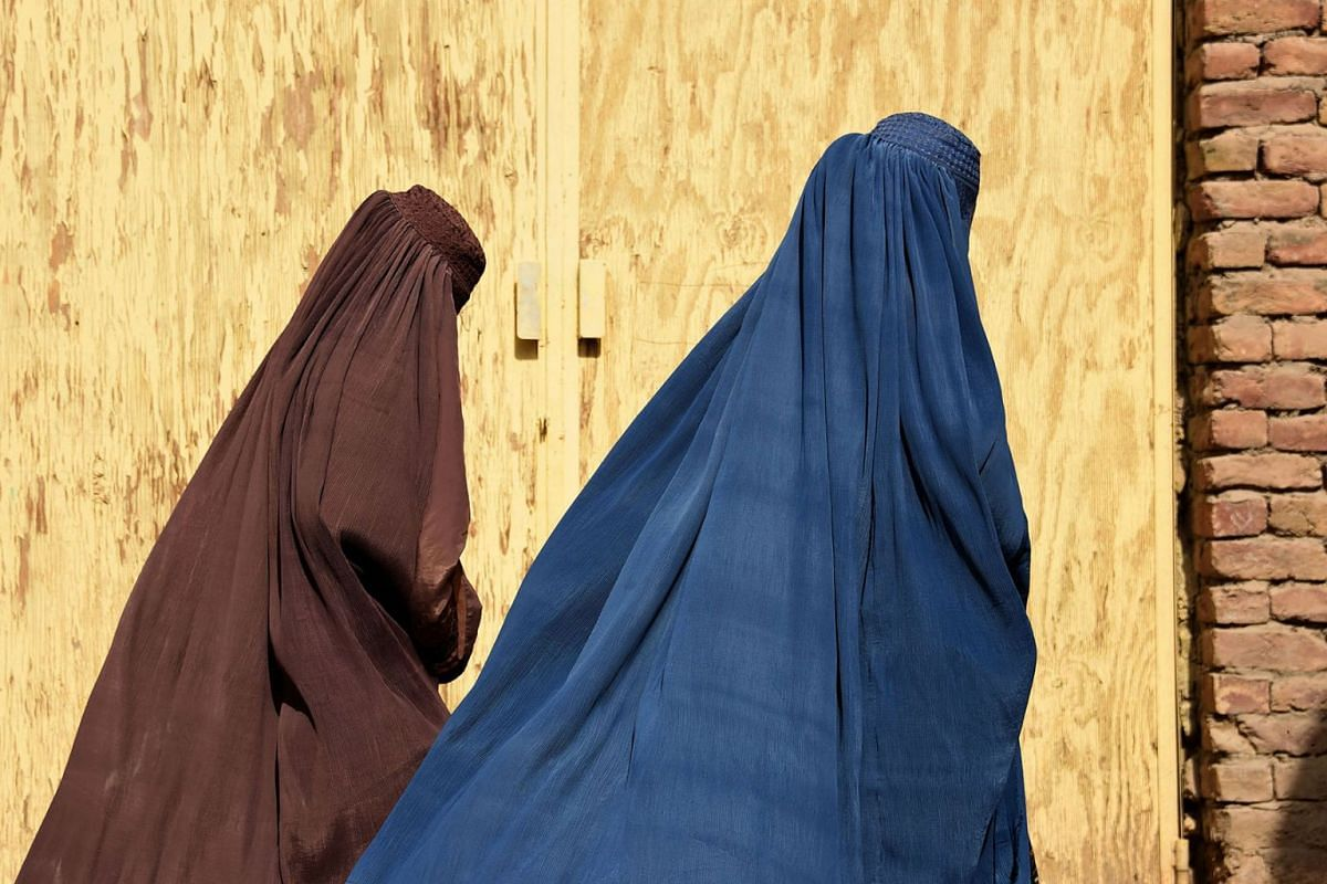 Afghan women wearing burqas from a polio immunisation team walk together during a vaccination campaign in Kandahar on October 15, 2019. PHOTO: AFP