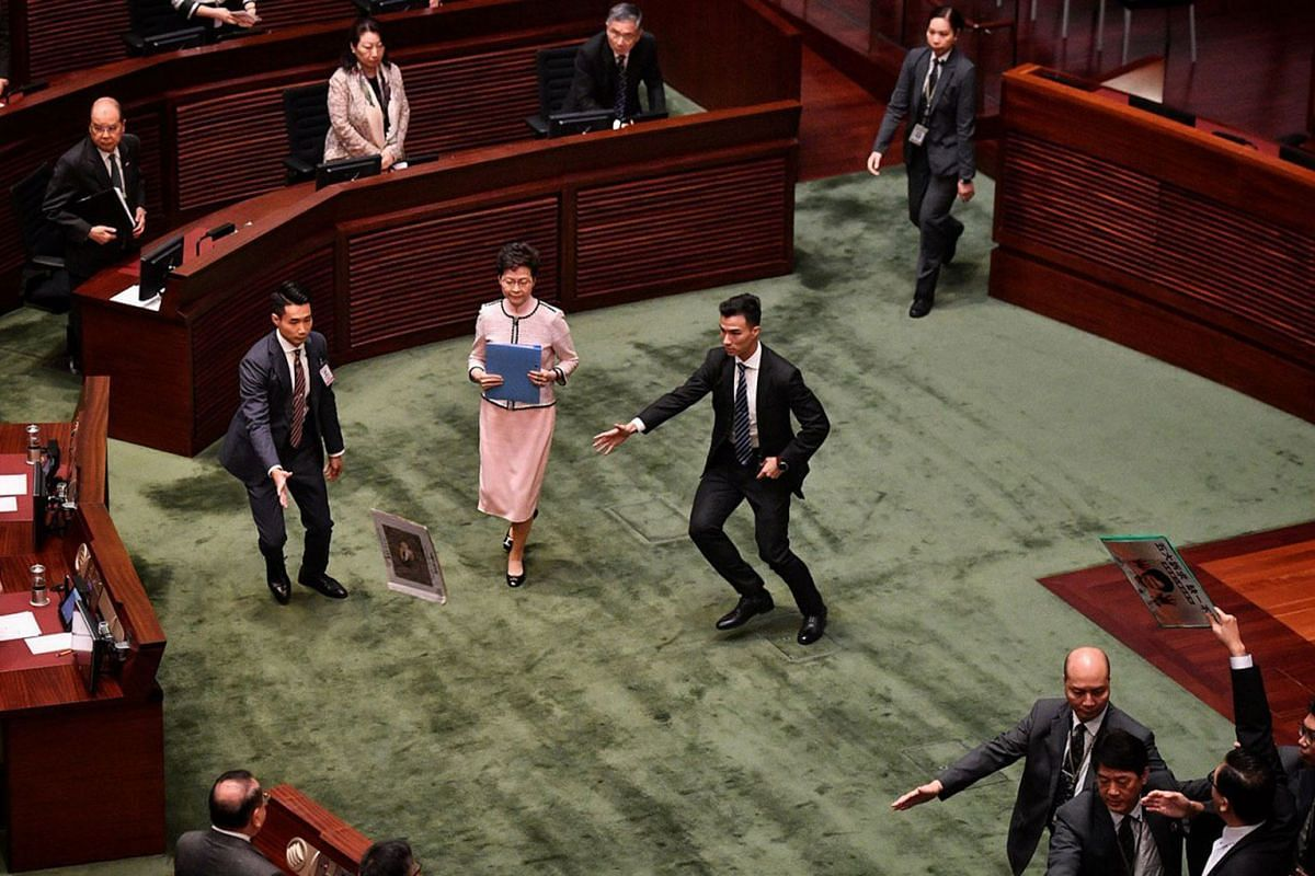 Security aides rushing to shield Hong Kong Chief Executive Carrie Lam after a pro-democracy legislator threw a placard at her while she was leaving the Legislative Council on Oct 16, 2019. Pro-democracy lawmakers disrupted Mrs Lam's annual policy a