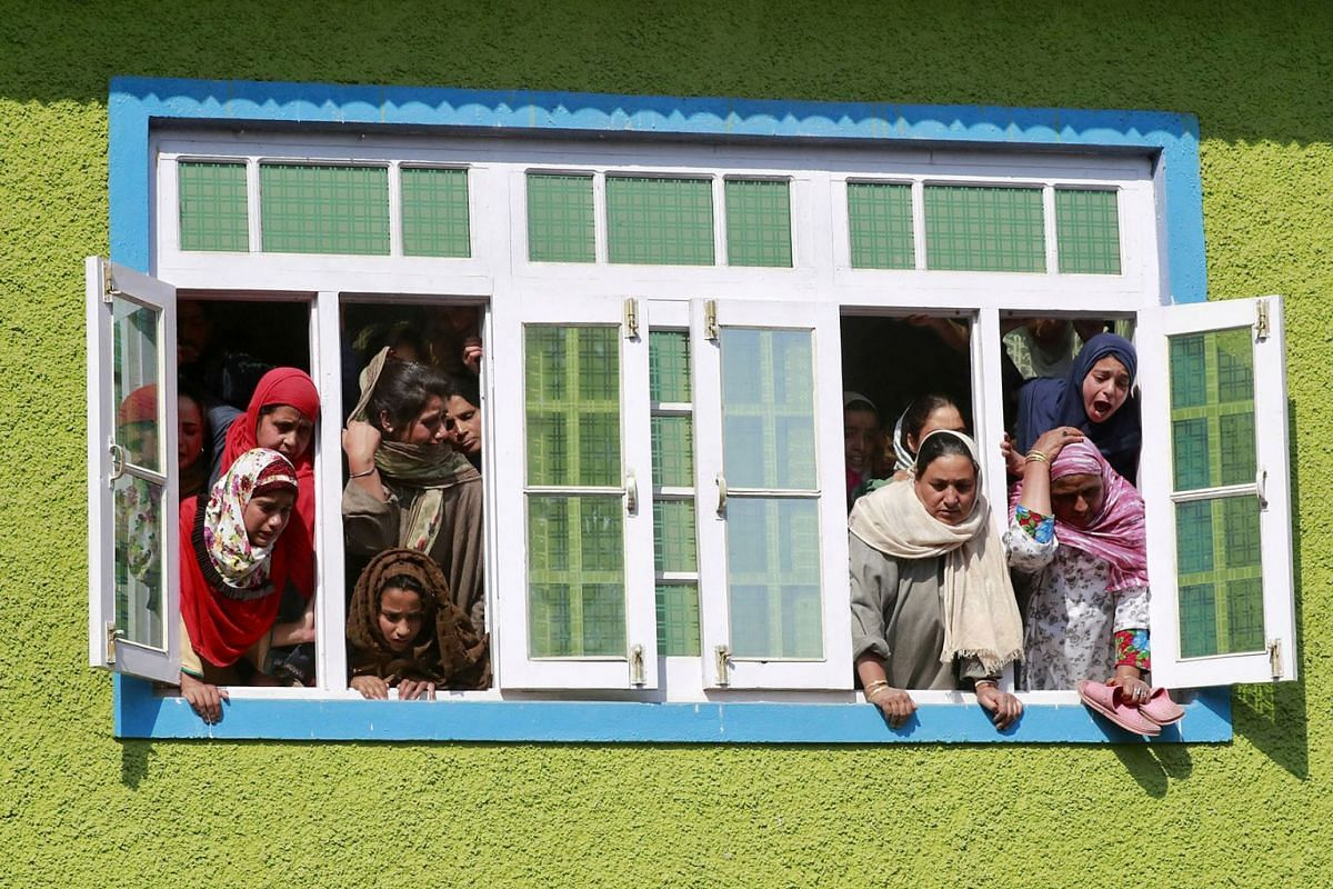 Kashmir women and girls react as they watch the body of Nasir Ahmad, a suspected separatist militant, during his funeral procession after he was killed in a gun battle with Indian soldiers, in Arwani village in south Kashmir's Anantnag district Octob