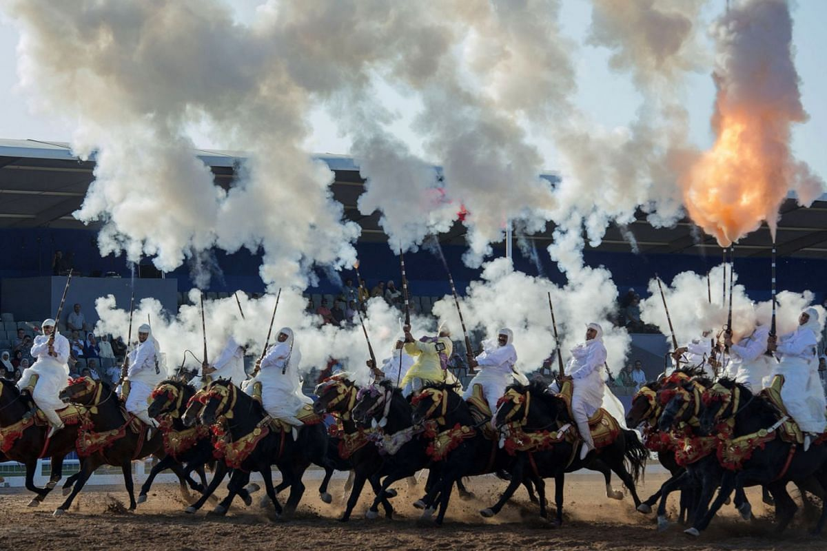 A troupe charges and fire their rifles loaded with gunpowder during a national competition for Tabourida,salon du cheval d'el jadida, in El Jadida, Morocco, October 15, 2019. PHOTO: EPA-EFE