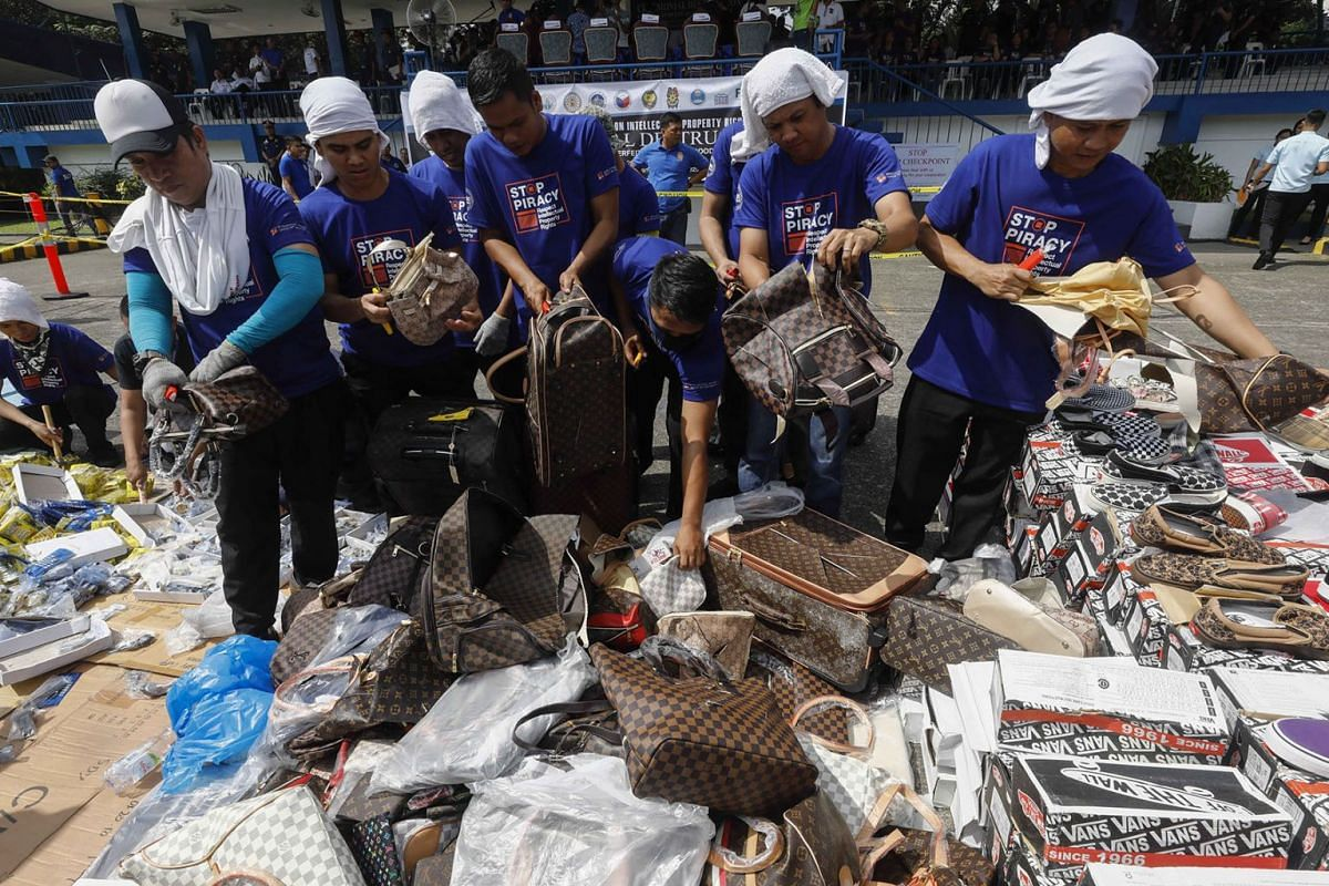Government workers cut up counterfeit bags during a ceremonial destruction of fake consumer goods worth 80.2 million pesos (1.4 million euro) at Camp Crame police headquarters in Quezon City, east of Manila, Philippines October 18, 2019. PHOTO: EPA-E