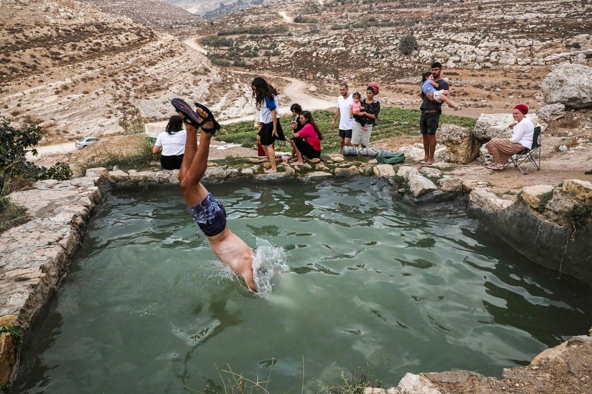 Israelis sit by as a man jumps into the pool of the natural water spring of Ein Farah (Ein Prat) in the Nahal Prat Nature Reserve of the Judean Desert in the Israeli-occupied Palestinian West Bank, East of Jerusalem, during the Jewish religious holid