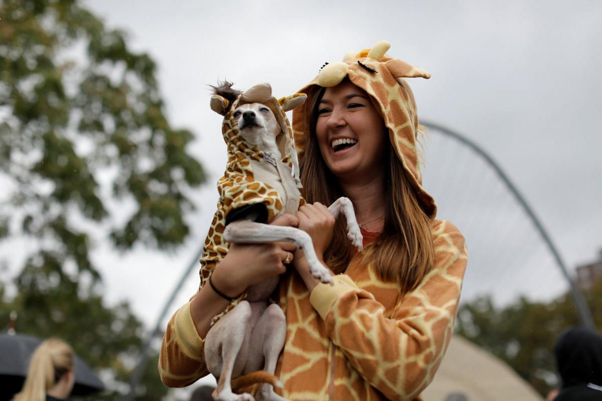 Ms Marcie Walker and her dog Nana both dressed as giraffes at the Tompkins Square Halloween Dog Parade in Manhattan, New York City, on Oct 20, 2019.