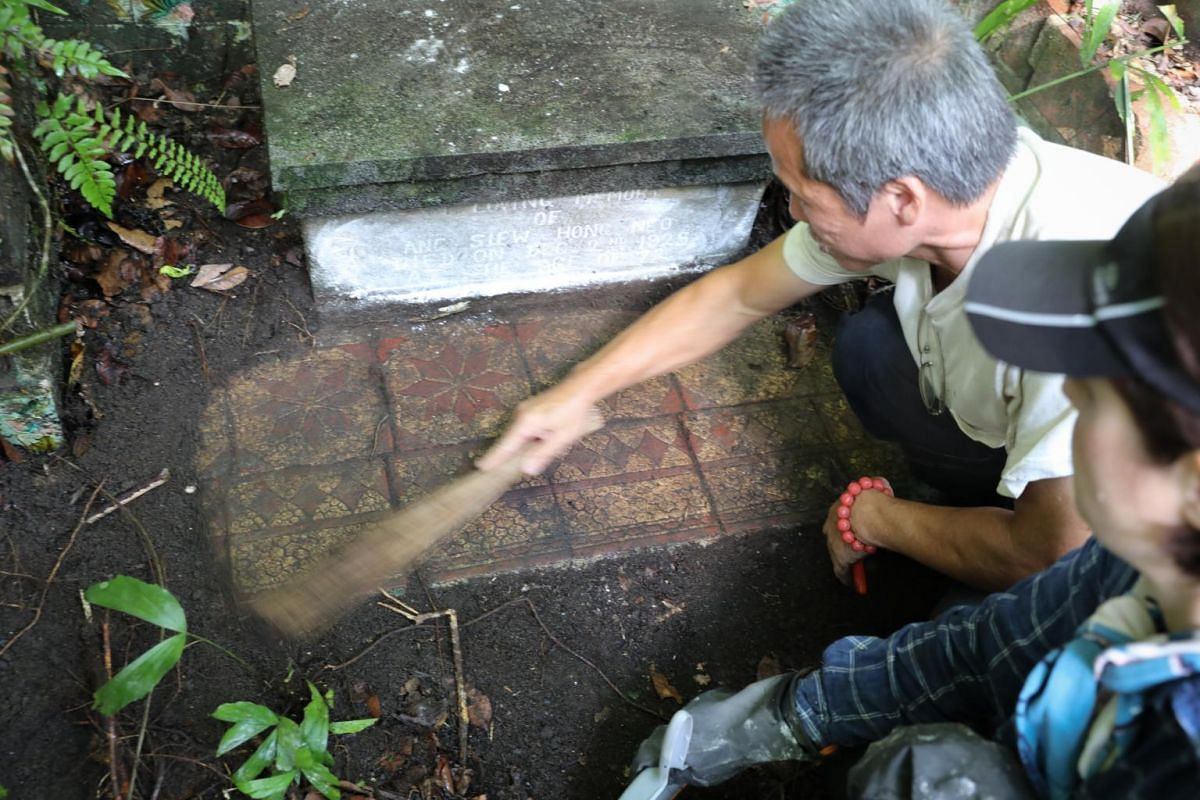 """Cemetery caretaker Soh Ah Beng sweeps the dirt to reveal tiles on the floor of the tomb. Not all tombs have floor tiles so whenever Jennifer finds one, it is a """"nice bonus"""", taken on Oct 4, 2019."""