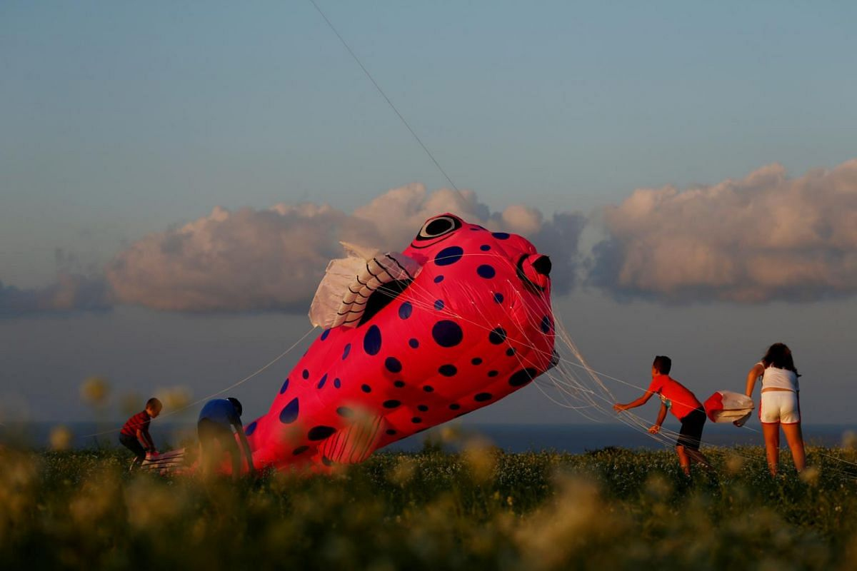 Children help to land a kite during the International Kite and Wind festival outside the village of Gharb, on the island of Gozo, Malta, on Oct 20, 2019.