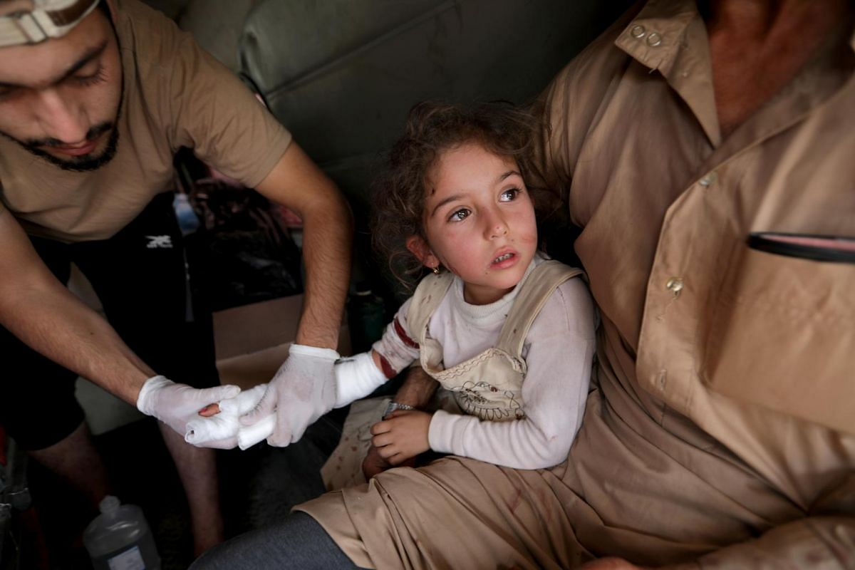 A wounded girl is treated in the town of Tal Abyad, Syria, Oct 20, 2019.