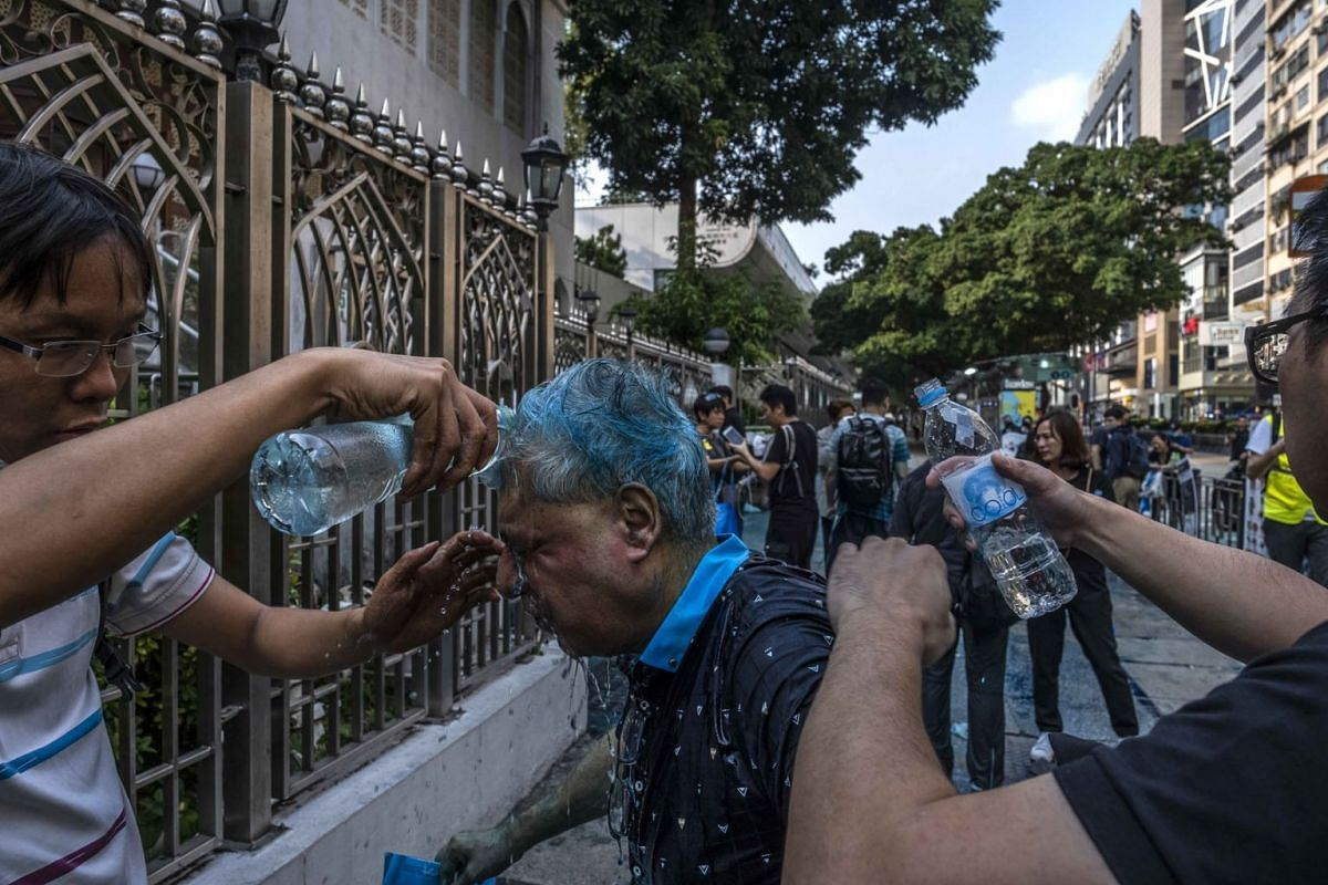 A man is helped after being sprayed with a blue liquid by police outside the Kowloon Mosque and Islamic Center in Hong Kong, Oct. 20, 2019. The police said the spraying of the mosque entrance had been an accident, and contacted the chief imam and Mus