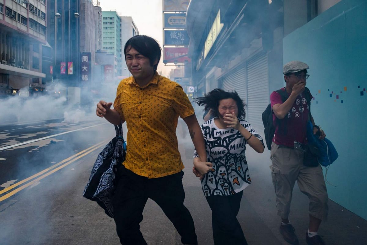 Protesters and bystanders along Nathan Road react from tear gas fired by police during a pro-democracy march in the Kowloon district in Hong Kong on October 20, 2019. PHOTO: AFP