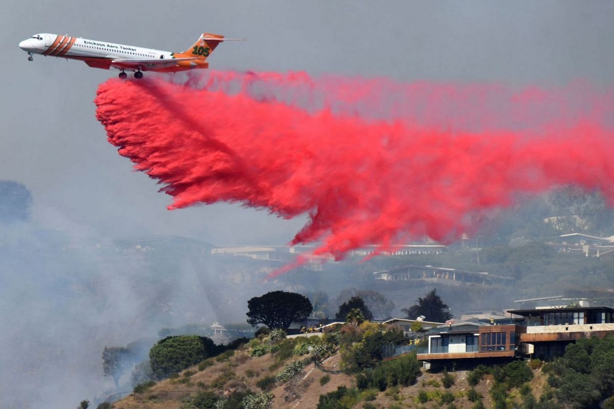 Firefighters battle a blaze from the air that was threatening homes in the Pacific Palisades community of Los Angeles, California, U.S., October 21, 2019. PHOTO: REUTERS