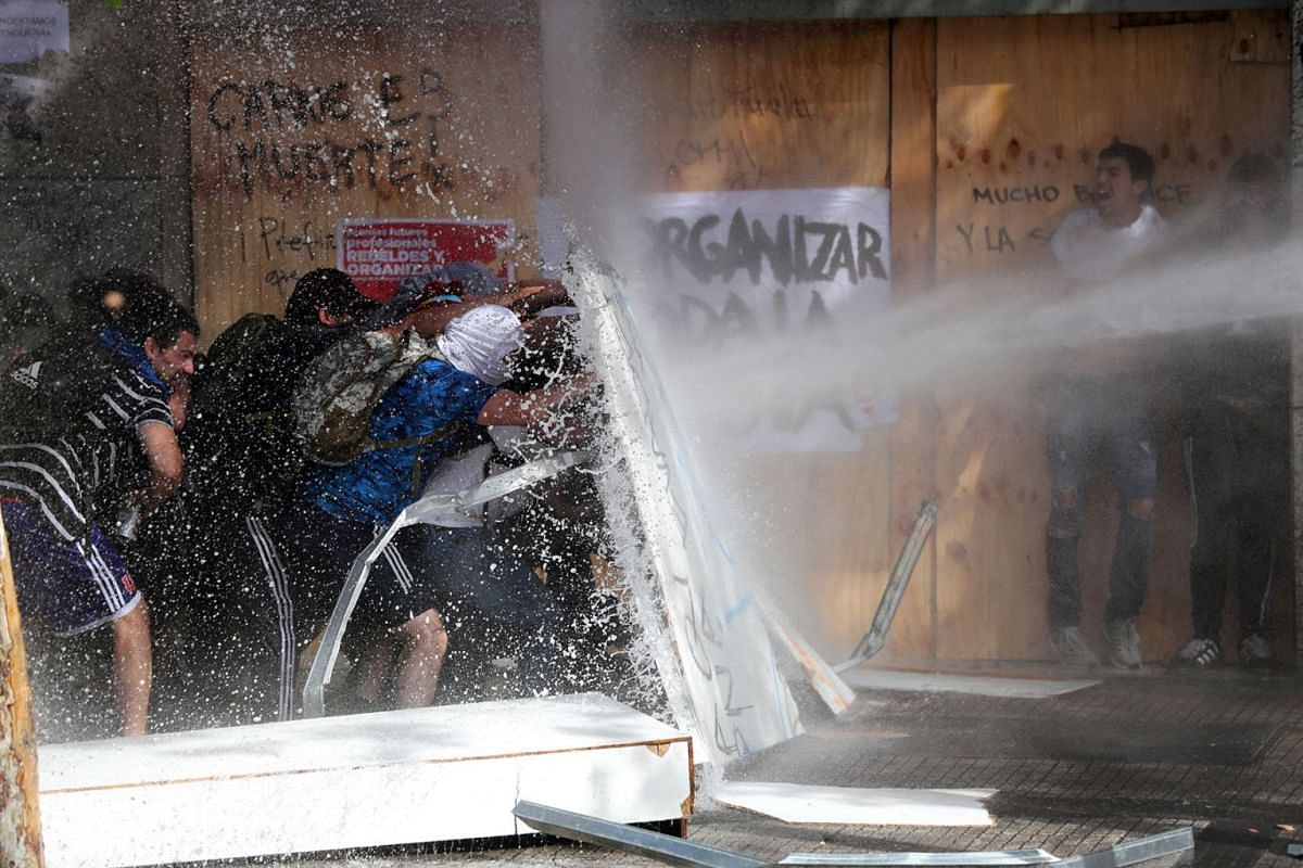 Demonstrators take cover as they are sprayed by security forces with a water cannon during a protest against Chile's state economic model in Santiago, Chile October 22, 2019. PHOTO: REUTERS