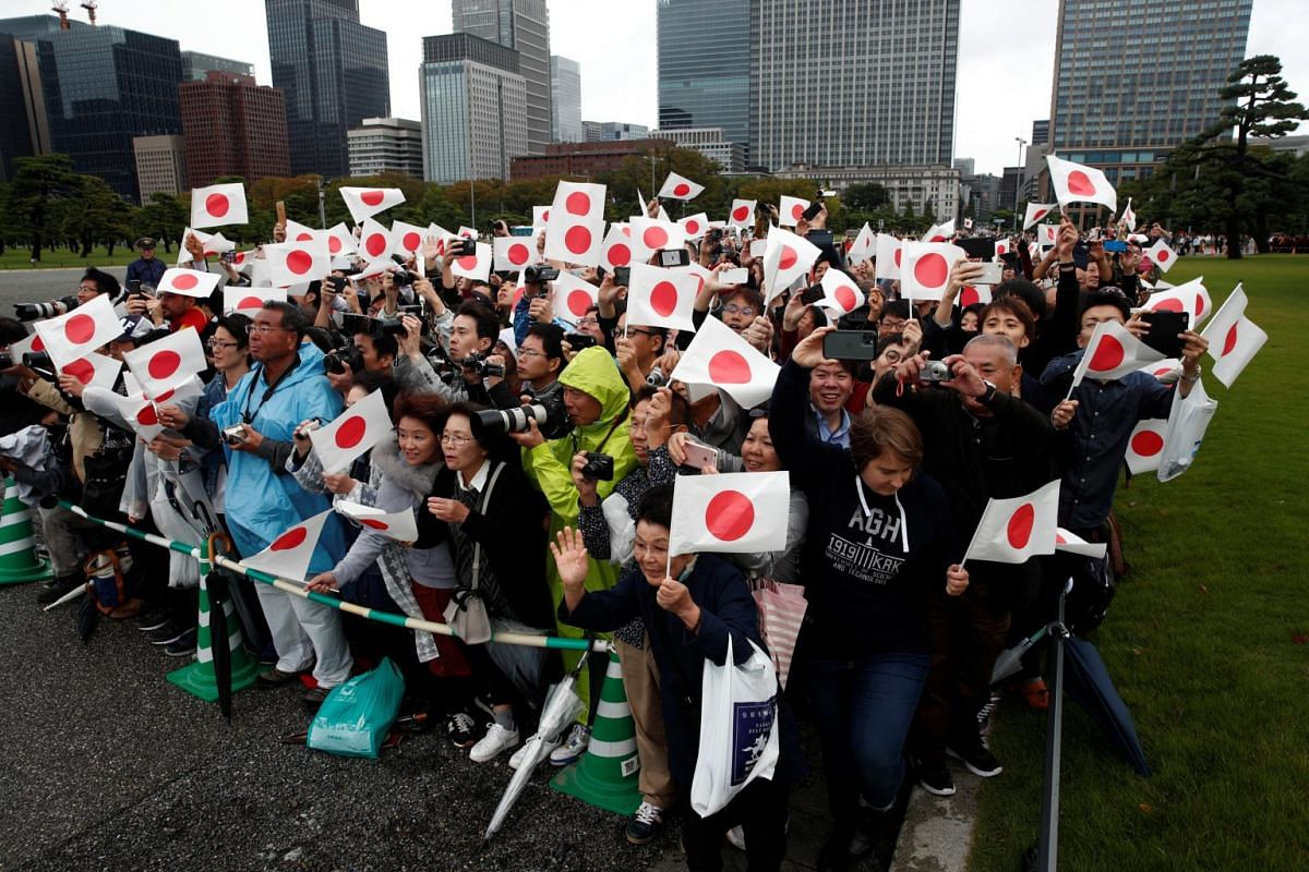 People wait for Japan's Emperor Naruhito to depart the Imperial Palace after the enthronement ceremony in Tokyo, Japan, on Oct 22, 2019.