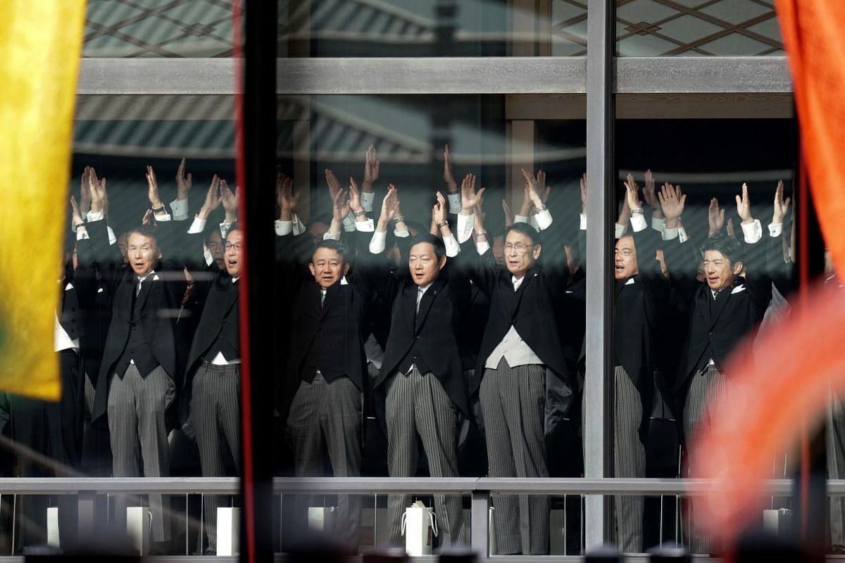 """Japanese officials shout """"banzai"""" (long live the Emperor) cheers for Emperor Naruhito and Empress Masako during the enthronement ceremony at the Imperial Palace in Tokyo on Oct 22, 2019."""
