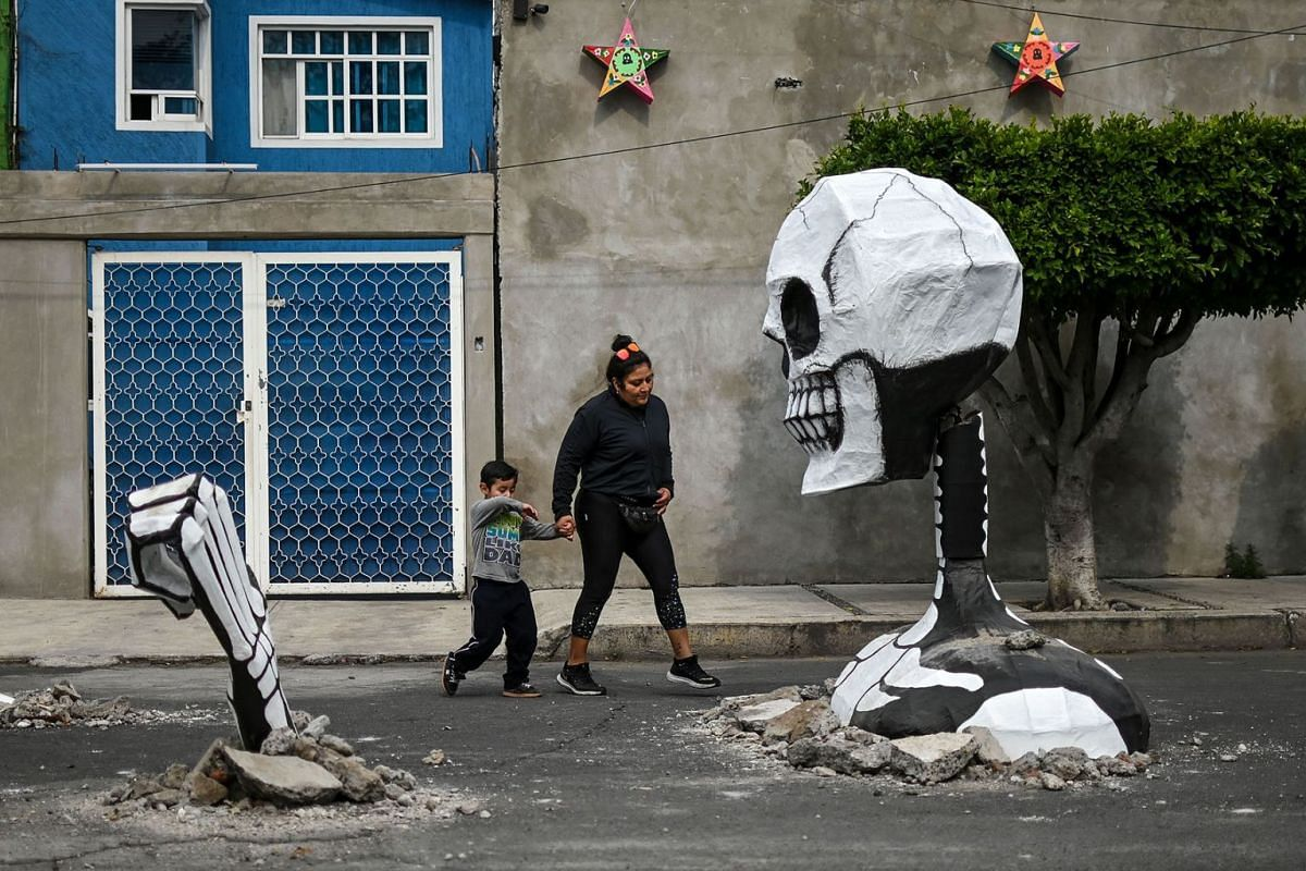 A woman and a child walk next to a huge cardboard skull made by artisans in a street in the Tlahuac neighbourhood, in Mexico City on Oct 28, 2019, ahead of the Day of the Dead celebrations.