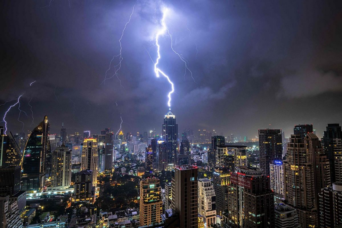Lightening strikes a building during a thunderstorm in Bangkok on Oct 27, 2019.