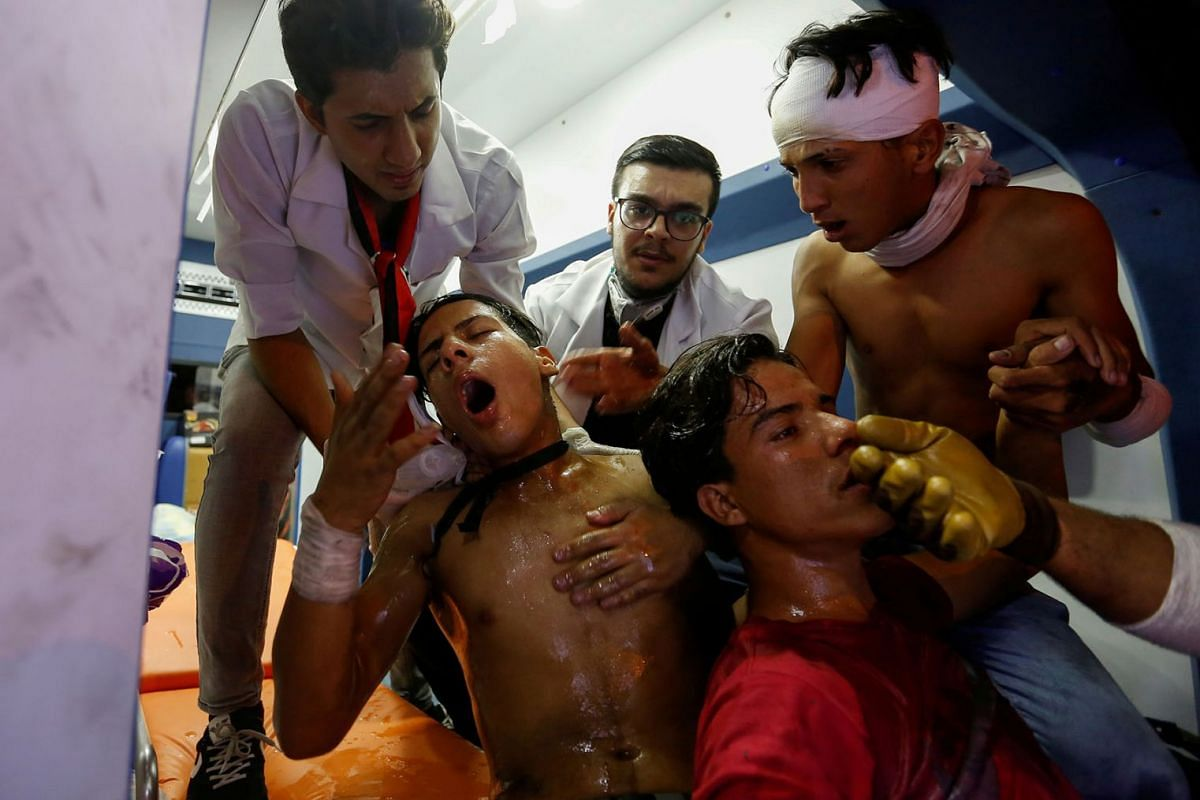Demonstrators who were affected by tear gas receive treatment from medical crew during a protest over corruption, lack of jobs, and poor services in Baghdad on Oct 29, 2019.