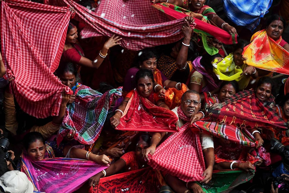 Hindu devotees collect rice as offerings distributed by the temple authority on the occasion of the Annakut, or Govardhan Puja, festival at the Madan Mohan temple in Kolkata, India, on Oct 29, 2019. People gather in large numbers at the temple and co