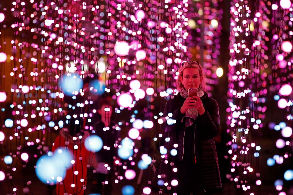 A woman takes photographs in an installation called 'submergence' which forms part of the River of Light festival in Liverpool, Britain, October 31, 2019.