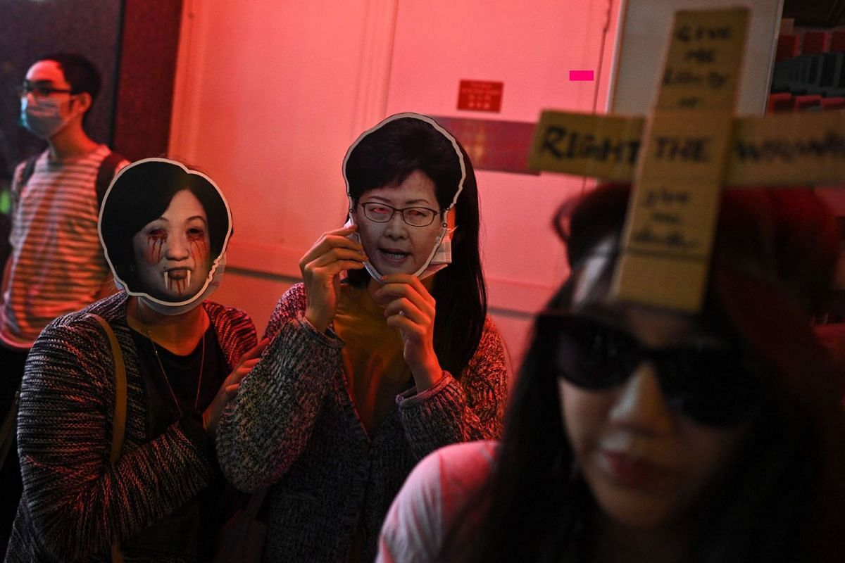 People wear a mask of pro-Beijing establishment lawmaker Regina Ip (left) and Hong Kong's chief executive Carrie Lam (centre) join a march to Central district during Halloween, in Hong Kong on October 31, 2019. Hong Kong democracy activists donned Ha