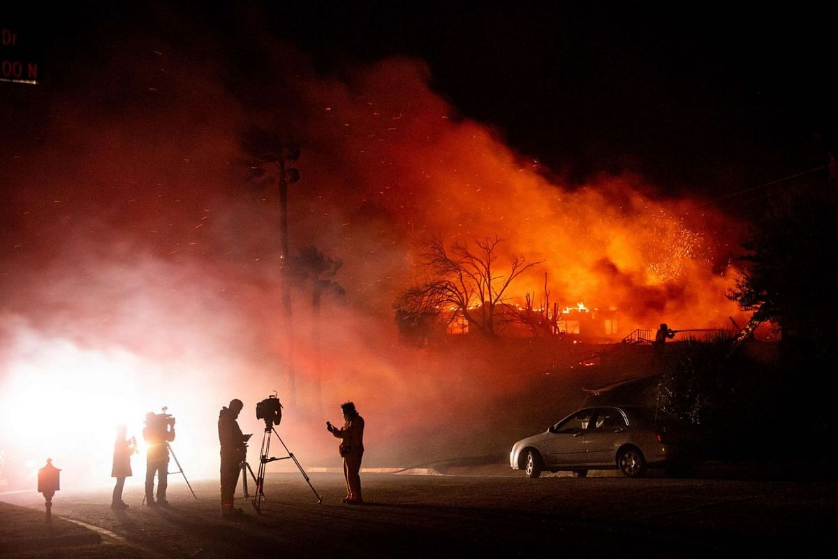 Media members report on a burning home as a firefighter douses flames (right) during the Hillside fire in the North Park neighborhood of San Bernardino, California on October 31, 2019. Firefighters battled new wildfires on in California including a f