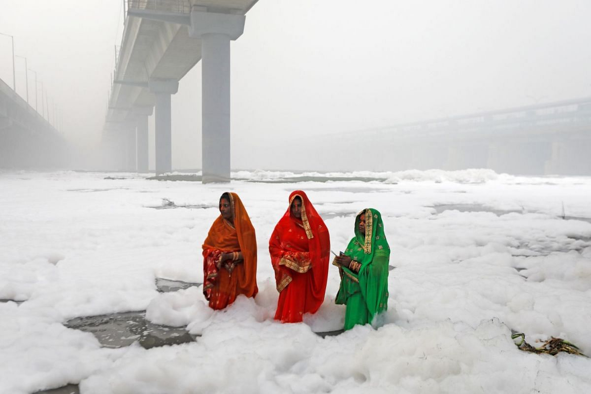 Hindu women worship the Sun god in the polluted waters of the river Yamuna during the Hindu religious festival of Chatth Puja in New Delhi, India on Nov 3, 2019.