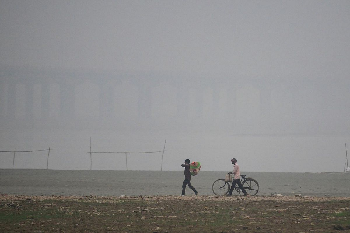 Men walk under heavy smog conditions along the Sangam, the confluence of the Yamuna and Ganges River, in Allahabad, on Oct 31, 2019.