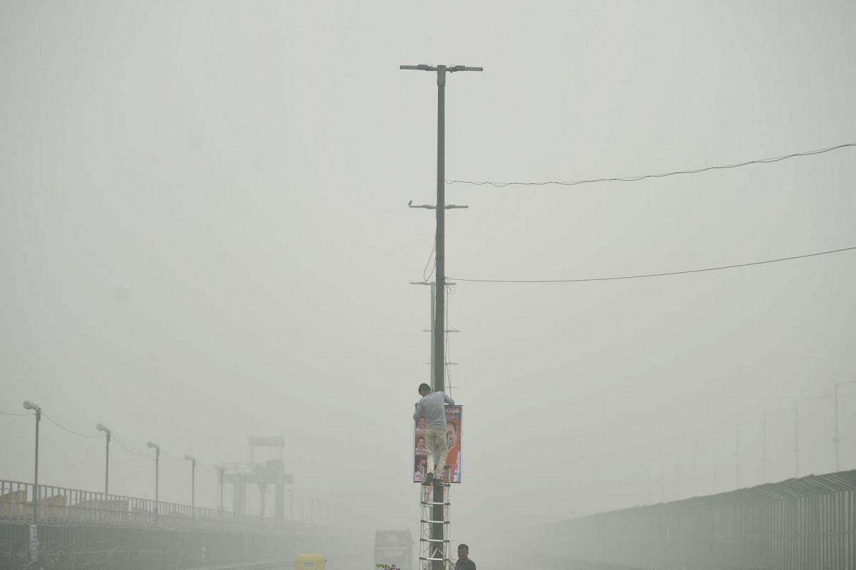 A man removes a hoarding from a lamp post in a flyover amid heavy smog conditions, in New Delhi, on Nov 3, 2019.