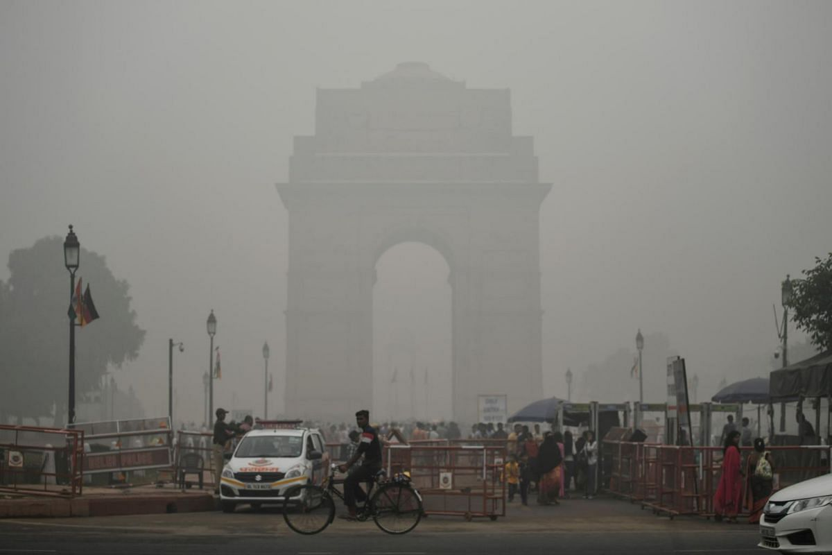 Tourists visit the India Gate under heavy smog conditions in New Delhi, on Nov 3, 2019.