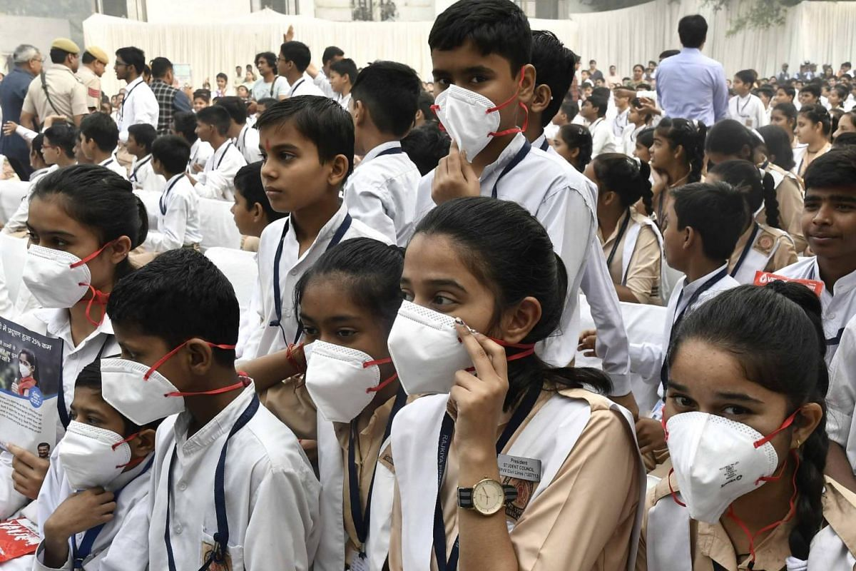 Indian school students wearing masks pose for a photograph after Delhi Chief Minister Arvind Kejriwal distributed masks in a government school in New Delhi, India, on Nov 1, 2019.