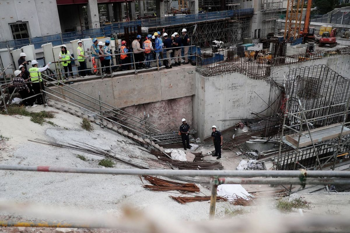 Police officers, with the body of the dead worker (foreground, covered by white sheet), at the work site in Novena yesterday. The Ministry of Manpower said the jib, or horizontal beam, of a tower crane had failed during a lifting operation. The polic