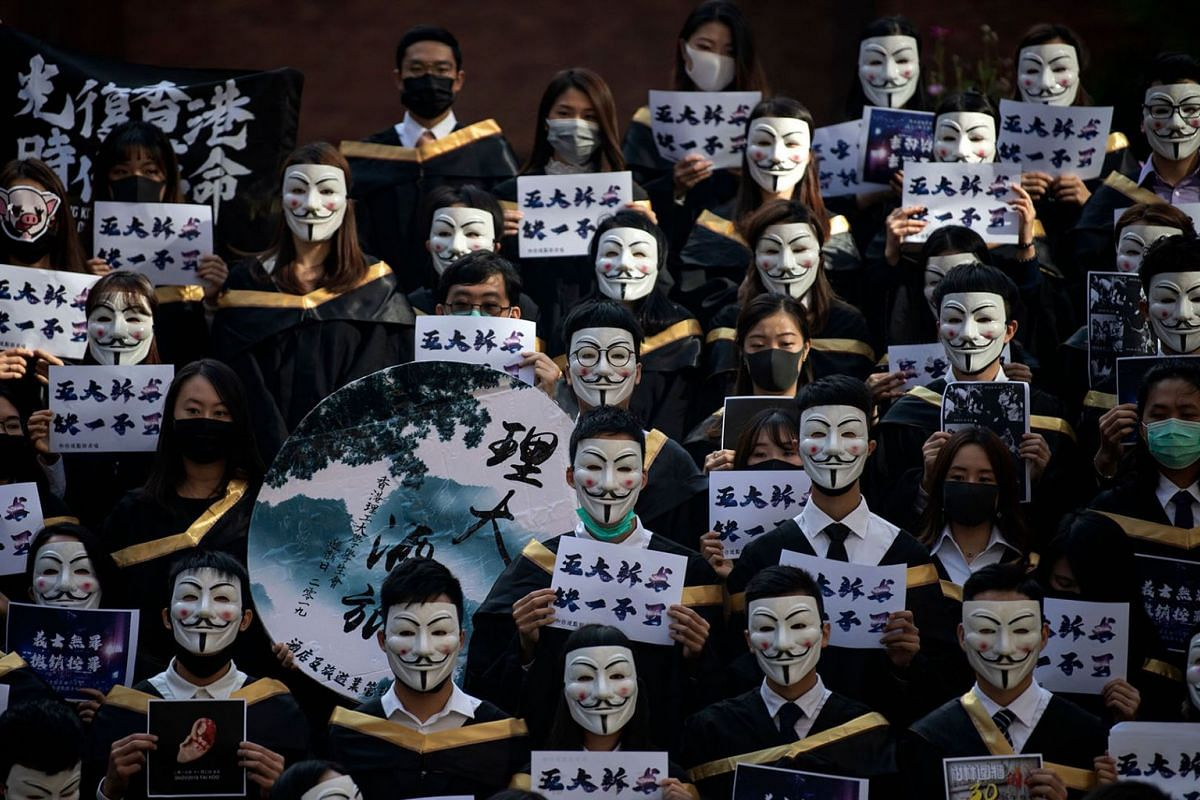 University students wear Guy Fawkes masks, popularised by the 'V For Vendetta' comic book film, before their graduation ceremony at the Hong Kong Polytechnic University in Hong Kong on Nov 5, 2019. It marks a month after a colonial-era Emergency Regu